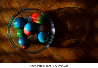 Vivid colored eggs for Easter standing in glass bowl on parquette floor