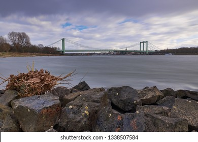Vivid colors - Panorama on the Rhine with rocks in the foreground and view over the Rhine to the Rodenkirchen bridge. There are strong winds over the city.