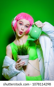 Vivid funny girl with pink hair wearing headphones holding a flower pot and a teapot. Green background. Beauty, fashion, youth style.