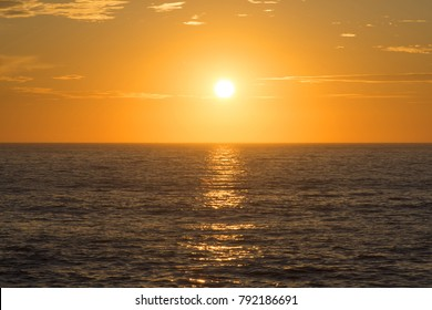Vivid golden sunset centered over open ocean horizon with calm surface