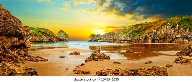 Vivid landscape of beach and coast with mountains and vegetation. Stunning scenery of coastline, beach and cliffs in Cantabria, Spain