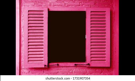 Vivid pink colored wooden window with opening shutters on brick wall