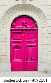 A vivid pink ornately decorated door and doorway in Paris. The architecture is traditional Parisian Haussmann.