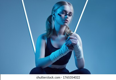 Vivid portrait of strong beautiful girl with blonde hair, sports figure, confident look and fists in protective boxing bandages posing on colorful neon light background