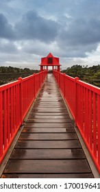 Vivid red bridge to red gazebo under dramatic sky after storm. Vivid color and heavy clouds. Way to destination. Pico island, Azores islands.