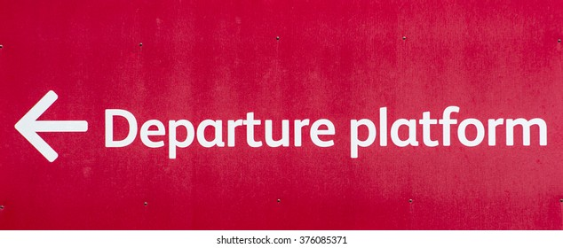 Vivid red sign pointing towards the Departure Platform