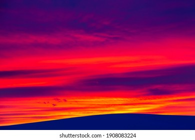 Vivid saturated beautiful sunset sky in pink, purple and blue colors with a mountain. Sunset background. - Shutterstock ID 1908083224