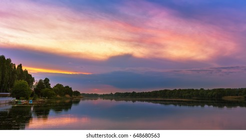 Vivid scenery of sunset at the river, colorful, dramatic evening sky reflected in the water. Khmelnytskyi, Ukraine.