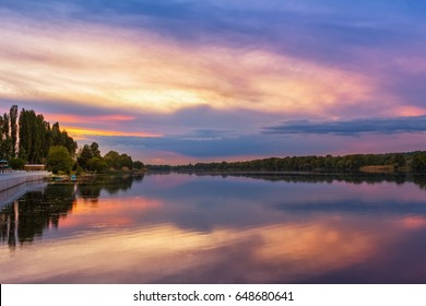 Vivid scenery of sunset at the river, colorful, dramatic evening sky reflected in the water, hdr image. Khmelnytskyi, Ukraine.