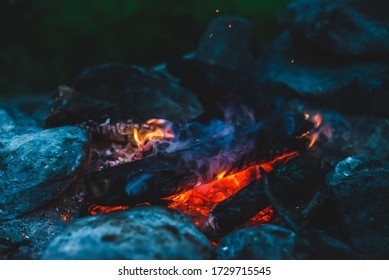 Vivid smoldered firewoods burned in fire close-up. Atmospheric warm background with orange flame of campfire. Unimaginable full frame image of bonfire. Burning logs in beautiful fire. Wonderful flame.