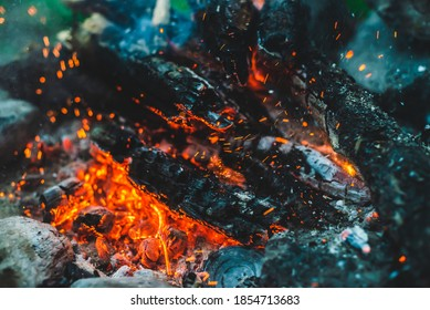 Vivid smoldered firewoods burned in fire close-up. Atmospheric background with orange flame of campfire. Full frame image of bonfire. Warm whirlwind of glowing embers and ashes in air. Sparks in bokeh