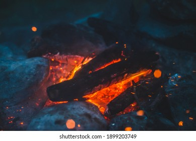 Vivid smoldered firewoods burned in fire closeup. Atmospheric background with orange flame of campfire. Wonderful full frame image of bonfire with glowing embers in air. Warm logs, bright sparks bokeh