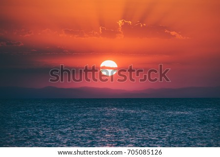 Vivid sunset through the clouds on a Greek beach
