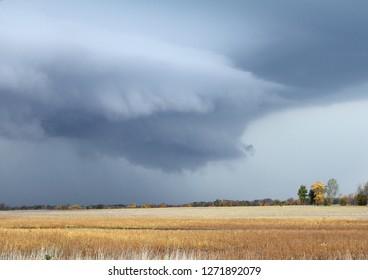 A vivid wall cloud looming over a farm field