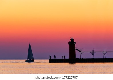 A vividly colorful twilight sky silhouettes a sailboat, people, and the lighthouse at South Haven, Michigan on Lake Michigan.