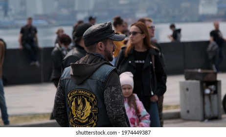 Vladivostok, Primorsky Territory, Russia - April 24 2021: a man in a cap and vest from a biker club night dragons walks among the crowd and looks around