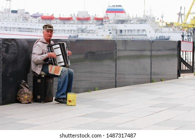 Vladivostok, Russia - 3 Jun 2019 : An elderly man plays the accordion on the waterfront to earn some money for a living. No one around.
