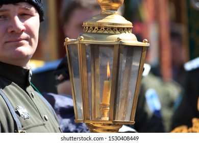 Vladivostok, Russia - April,8,2019: Cossack holding the Holy Fire brought from Jerusalem during the procession on Easter.