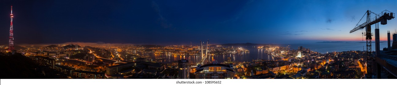 Vladivostok, Russia - High resolution city panoramic nightscape of Vladivostok, the center of APEC Forum '2012. Shoot on May 29, 2012. The final stage of bridge construction