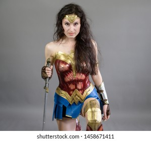 VLADIVOSTOK, RUSSIA - JULY 20, 2019: Festival on the game and a series of books series Witcher. Cosplayer as Wonder woman from DC movies and comic posing against grey background.