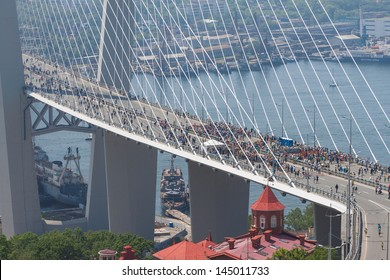 "VLADIVOSTOK, RUSSIA - JULY 7: Flashmob ""I love Vladivostok"" on the ""Golden Bridge"". 26,904 people who have created a ""live"" 707-meter Russian flag on July 7, 2013 in Vladivostok, Russia."