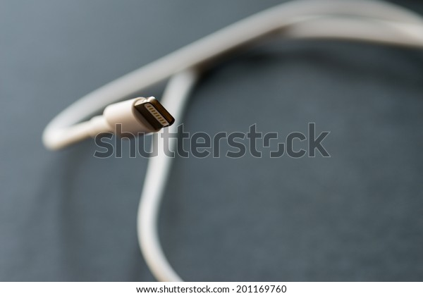 VLADIVOSTOK, RUSSIA - JUNE 4, 2014: Apple Lightning Connector on dark background. Is a proprietary connector used to connect mobile devices  such as iPhones, iPads or iPods to computers.