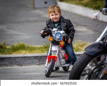VLADIVOSTOK, RUSSIA, October 03, 2015: A happy little boy driving a  toy motorcycle in closing-time of a motorcycle season in Vladivostok.