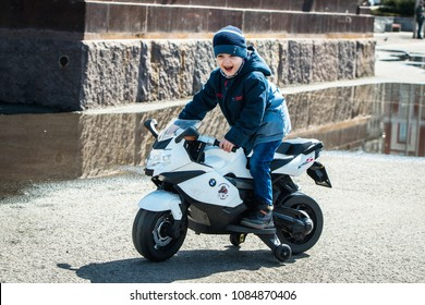 Vladivostok, Russia - on May 05, 2018: A happy little boy driving a  toy motorcycle during the holiday on the occasion of opening of a season of motorcycles.