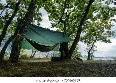 VLADIVOSTOK, RUSSIA - SEPTEMBER 25, 2017: Expedition along the north-east coastline of Russia. Hammock under the tent on a rainy day.