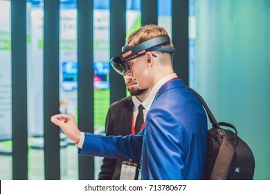Vladivostok, Russia - September 7, 2017: Young man wearing virtual reality headset or goggles looking around and trying to touch something Microsoft HoloLens. VR