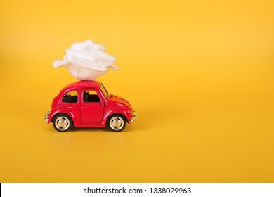VLASOTINCE, SERBIA- MARCH 11, 2019: :Red retro toy car with white rose flower on yellow background. Flowers, gifts delivery concept. Valentine's day, Birthday, woman day, engagement.