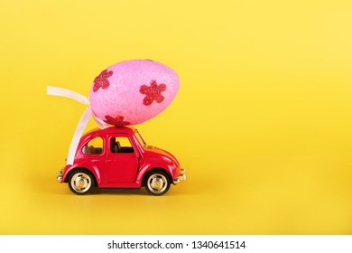 VLASOTINCE, SERBIA- MARCH 11, 2019: Easter holiday concept with egg on toy red car on yellow background