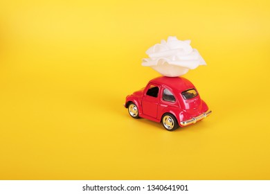 VLASOTINCE, SERBIA- MARCH 11, 2019: Red retro toy car with white rose flower on yellow background. Flowers, gifts delivery concept. Valentine's day, Birthday, engagement.