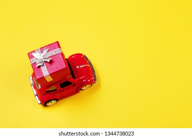 VLASOTINCE, SERBIA- MARCH 11, 2019: Red retro toy car with gift box on yellow background. Flowers, gifts delivery concept. Valentine's day, Birthday, engagement. Top view.