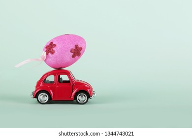 VLASOTINCE, SERBIA- MARCH 11, 2019: Easter holiday concept with egg on toy red car on turquoise background