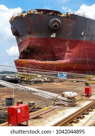 A VLCC (tanker) damaged in a collision in the congested waters of Singapore Strait, lies at a repair yard in Sembawang. The damage will be cropped and a new bow fabricated.