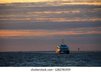 Vlieland ferry crossing the Waddenzee at sundown, orange sky.