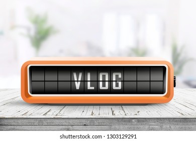 Vlog word written on a retro device in orange color in a bright room