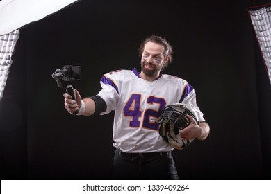 Vlogger in American football player uniform online in social networks using a mobile phone on the stabilizer recording video blog.