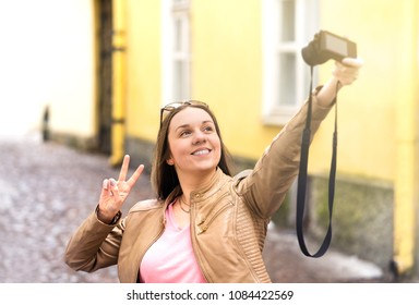 Vlogger filming video blog in city. Young smiling happy woman making vlog or taking selfie with camera. Showing v sign hand gesture.
