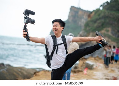 Vlogger holds and smile with his camera