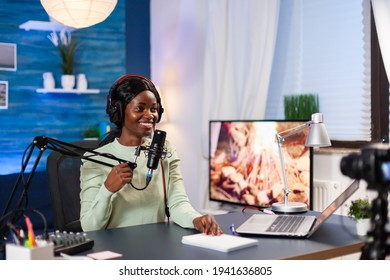 Vlogger talking with her audience while making online show from living room. Speaking during livestreaming, blogger discussing in podcast wearing headphones.