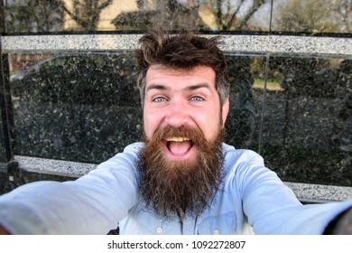 Vlogging concept. Man, tourist with beard and mustache on cheerful, smiling face, black marble background. Hipster, tourist with tousled hair and long beard looking at camera, taking selfie photo