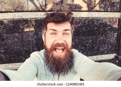 Vlogging concept. Man, tourist with beard and mustache on cheerful, smiling face, black marble background. Hipster, tourist with tousled hair and long beard looking at camera, taking selfie photo.