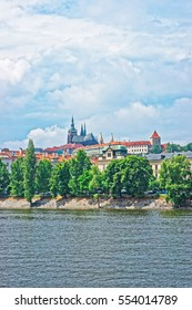 Vltava River embankment with Prague Old Town, Czech Republic. Strakova Academy with St Vitus Church on the background