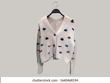 V-neck cardigan with long sleeves, contrast floral crochet applique and a button-up front on a hanger isolated on beige background. Composition of clothes. Banner concept. Trendy clothes collage
