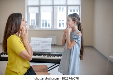 Vocal lesson. Girl in blue dress and her teacher doing voice exercises