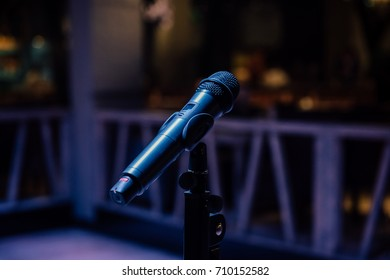 Vocal microphone on stand on scene at party in night club.Live music show,mic for singer in bright stage light.Concert lighting.Professional vocal mic on concert stage.Vertical