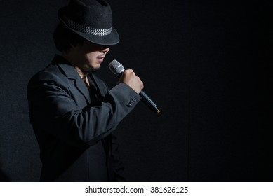 Vocalist holding microphone in dark,low key image