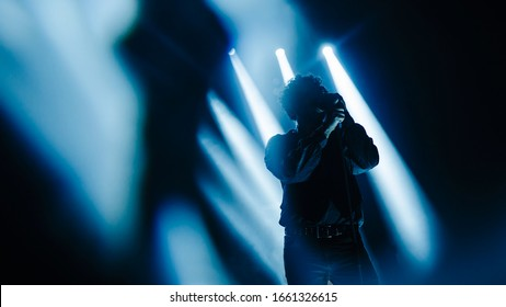 vocalist performing on stage at a concert in the fog. Dark background, smoke, concert  spotlights.